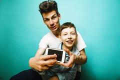 Modelo bonito novo do homem com o filho bonito pequeno que joga junto, li foto de stock