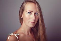 Modelo bonito novo louro caucasiano pensativo calmo da mulher da menina com cabelo e olhos azuis longos no vestido branco Foto de Stock