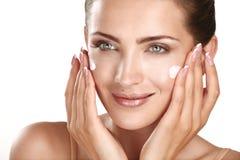 Modelo bonito que aplica treatmen de creme cosméticos em sua cara Foto de Stock Royalty Free