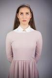 Modelo bonito serio con el vestido rosado en la mirada para arriba Imagenes de archivo