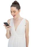 Modelo bonito sonriente en el vestido blanco que envía el mensaje de texto Imágenes de archivo libres de regalías