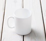 Modelo branco do copo na tabela de madeira fotos de stock royalty free