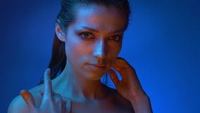 Modelo brillante con el maquillaje del brillo que se coloca en tactos de luces de neón azules la clavícula que mira en cámara  metrajes