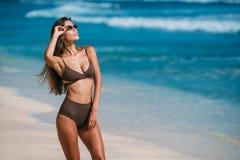 Modelo bronceado atractivo con las gafas de sol en el traje de baño marrón que presenta en la playa arenosa blanca fotos de archivo