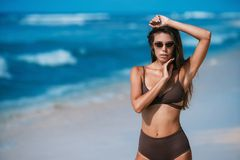 Modelo bronceado atractivo con las gafas de sol en el traje de baño marrón que presenta en la playa arenosa blanca fotos de archivo libres de regalías