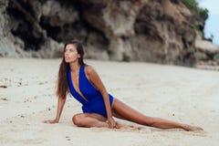 Modelo bronceado atractivo en el traje de ba?o azul que presenta en la playa arenosa blanca fotos de archivo libres de regalías
