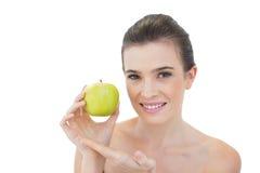 Modelo cabelludo marrón natural atractivo que muestra una manzana verde Foto de archivo