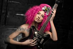 Modelo caucásico atractivo joven de la muchacha con el pelo rosado brillante rizado del estilo afro, la cara tatuada y las flores fotografía de archivo