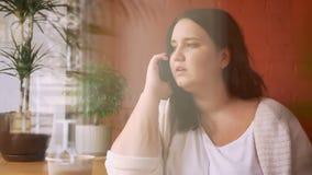 Modelo caucásico pesado que habla sobre el teléfono en café con la taza de café cerca de ventana metrajes