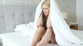 Modelo caucasiano novo comprimido que levanta na cama acolhedor envolvida na cobertura morna filme