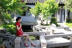 Modelo chino del cheongsam en jardín clásico chino imagenes de archivo