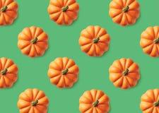 Modelo colorido de calabazas anaranjadas en fondo verde foto de archivo libre de regalías
