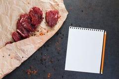 Modelo com bife da carne no papel e nas especiarias Fotografia de Stock
