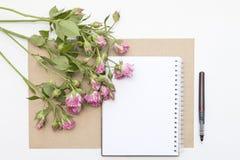 Modelo com bloco de notas vazio e poucas rosas do rosa de jardim workspace fotos de stock