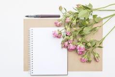 Modelo com bloco de notas vazio e poucas rosas do rosa de jardim workspace imagens de stock royalty free
