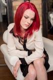 Modelo com cabelo vermelho vívido na cadeira Fotografia de Stock