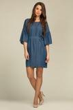Modelo com o vestido vestindo das calças de brim do penteado encantador fotos de stock