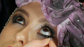 Modelo com os olhos marrons que aplicam o close up do lápis de olho O profissional compõe o artista que aplica o lápis de olho pr video estoque