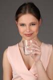 Modelo con el agua potable del maquillaje Cierre para arriba Fondo gris Imagen de archivo libre de regalías