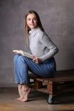 Modelo con el libro que se sienta en un tablero Fondo gris Imagen de archivo