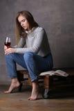 Modelo con el vidrio de vino que mira abajo Fondo gris Foto de archivo