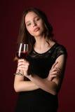 Modelo con el vino y los brazos cruzados Cierre para arriba Fondo rojo oscuro Foto de archivo