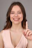 Modelo con la crema que muestra un finger Cierre para arriba Fondo gris Fotos de archivo