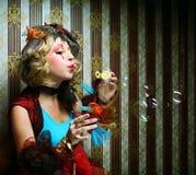 modelo con las burbujas de jabón del maquillaje que soplan creativo. Fotografía de archivo libre de regalías
