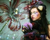 modelo con las burbujas de jabón del maquillaje que soplan creativo. Fotos de archivo libres de regalías