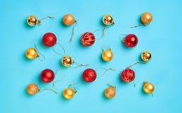 Modelo con oro de la Navidad y bolas rojas en un fondo azul Fotos de archivo libres de regalías
