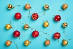 Modelo con oro de la Navidad y bolas rojas en un fondo azul Imágenes de archivo libres de regalías