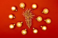 Modelo creativo de la decoración de las chucherías múltiples de la Navidad con la rama de árbol de oro de pino en el fondo rojo imagen de archivo