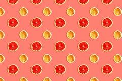 Modelo creativo de rebanadas de pomelo y de limón en el fondo coralino foto de archivo