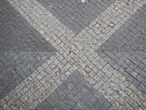 Modelo cruzado en un pavimento de adoquín de la calle Fotos de archivo
