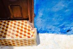 Modelo a cuadros en las escaleras con la pared azul imagenes de archivo