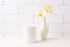 Modelo da caneca de café branco com a orquídea amarela macia no vaso Imagens de Stock Royalty Free