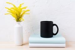 Modelo da caneca de café preto com grama e os livros dourados decorativos Fotografia de Stock