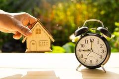 Modelo da casa da captura do homem e a pilha do despertador no fundo de madeira da tabela e do por do sol no momento da mostra do foto de stock royalty free