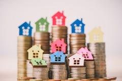 Modelo da casa na pilha das moedas Dinheiro planejando das economias das moedas para comprar um conceito, uma hipoteca e uns orga fotografia de stock