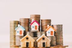 Modelo da casa na pilha das moedas foto de stock