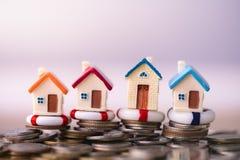 Modelo da casa nos boia salva-vidas na pilha das moedas fotografia de stock royalty free