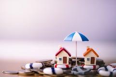 Modelo da casa nos boia salva-vidas na pilha das moedas imagem de stock