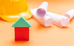 Modelo da casa pequena, capacete de segurança e modelos do projeto no fundo alaranjado da cor fotos de stock
