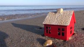 Modelo da casa pequena na areia da praia do oceano vídeos de arquivo