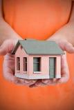 Modelo da casa pequena na mão humana Fotos de Stock