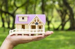 Modelo da casa da terra arrendada do homem em sua mão O conceito da construção imagem de stock royalty free