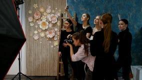 Modelo da jovem mulher que tem uma sessão de foto no estúdio Um tiro do fotógrafo quando outros modelos que tomam um selfie vídeos de arquivo