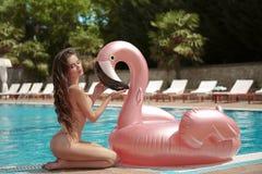 modelo da menina do biquini que aprecia no colchão inflável do flutuador da associação do flamingo do rosa do lilo no roupa de ba fotografia de stock royalty free