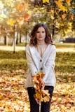 Modelo da mulher com as folhas da queda em Autumn Park Outdoors fotos de stock