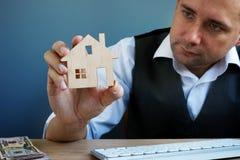 Modelo da terra arrendada do homem da casa Investimento da propriedade e hipoteca da casa foto de stock